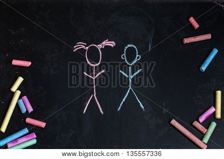 colored chalks on a black blackboard with the drawings of little girl and boy