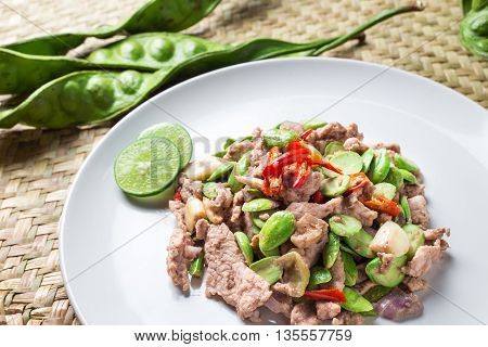 Thai Food Pad Sa tor Ka pi Moo (Fired Parkia speciosa beans with Shrimp paste and pork) traditional meal from South of Thailand ingredient on natural wicker mat background