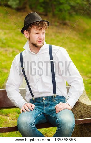 Fashion. Young fashionable man retro style wearing denim pants with straps sitting on bench in park outdoor