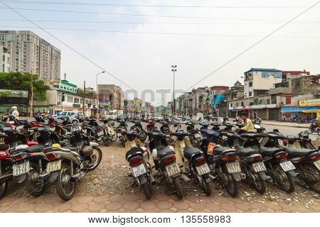 Hanoi, Vietnam - October 18, 2014: Motorbikes and a caretaker at parking lot in a typical Hanoi neighborhood.