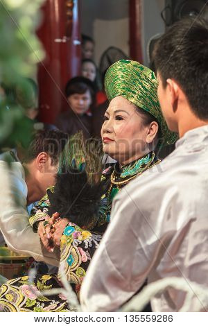 Thanh Hoa, Vietnam - October 19, 2014: A female medium is being dressed up to perform Len Dong, a spirit mediumship ritual in Central Vietnam. In trance the medium channels gods and goddesses of the Dao Mau religion.