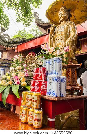 Thanh Hoa, Vietnam - October 19, 2014:Offerings of tea, Coco Cola and beer stand in front of a statue of Guanyin, the spiritual figure of mercy and mother goddesses, in front of a temple in Central Vietnam.