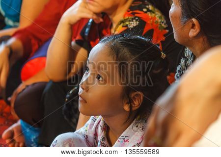 Thanh Hoa, Vietnam - October 19, 2014: A young girl watches a religious Dao Mau ceremony (spirit mediumship) in Central Vietnam.