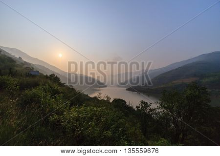 Lush vegetation, mountains and lake at sunrise in Yunnan province, China.