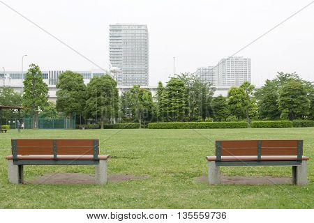 Two Wooden Benches And Grass Floor In Public Park