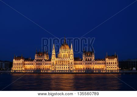 Hungarian Parliament along the Danube River in Budapest in the evening blue hours illuminated by warm lighting