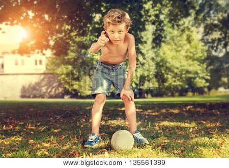 Boy ready to kick ball in park