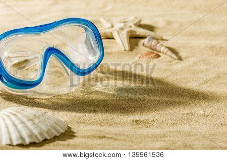 A diving mask on the beach in the sand
