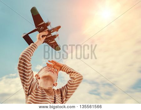Boy with toy plane with sky background