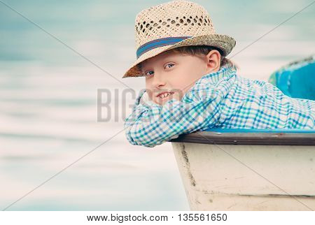 Boy in old boat portrait at the contryside