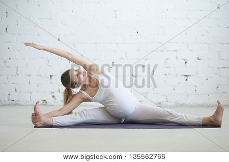 Pregnant Young Woman Doing Prenatal Yoga. Side Bend In Seated Splits Exercise
