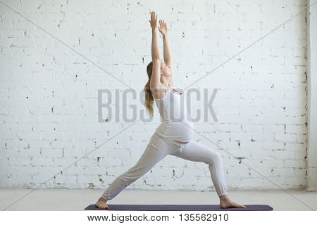 Pregnant Young Woman Doing Prenatal Yoga. Warrior One Pose