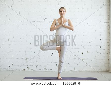 Pregnant Young Woman Doing Prenatal Yoga. Tree Pose