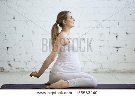 Pregnant Young Woman Doing Prenatal Yoga Hero Pose, Virasana