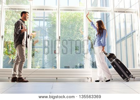 Full length of woman with luggage waving to her boyfriend. Young male and female partners are at airport. They are in casuals.