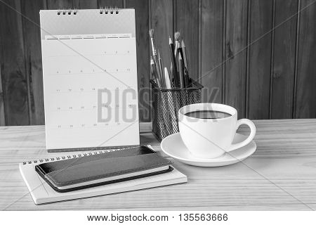 Black and white note book coffee cupand stack of book with calendar on wooden table background. Business concept