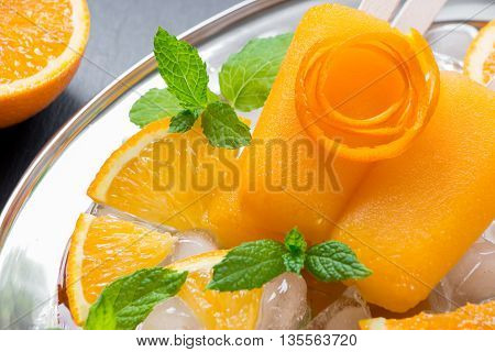 Orange sorbet ice cream decorated with a flower of orange peel mint leaves on silver plate with ice cubes orange slices on black background. Orange sorbet ice cream popsicles. Horizontal. Close.