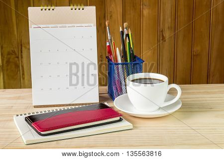 Note book coffee cup and stack of book with calendar on wooden table background. Business concept