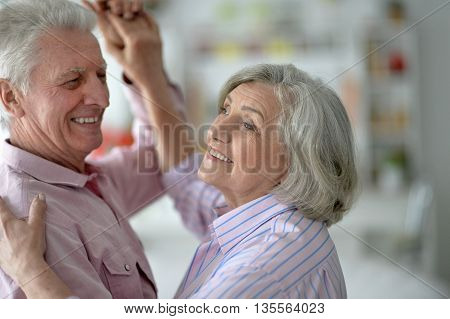 Portrait of a happy senior couple dancing at home