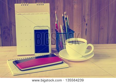 Note booksmart phonecoffee cupand stack of book with calendar on wooden table background.vintage tone