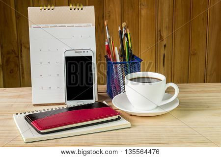 Note booksmart phonecoffee cupand stack of book with calendar on wooden table background