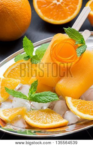 Orange sorbet ice cream decorated with a flower of orange peel on silver plate with ice cubes orange pieces mint near orange slices on black background. Orange sorbet ice cream popsicles. Vertical.