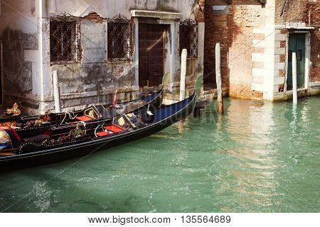 two empty gondolas near old building wall in channel waters in Venice Italy