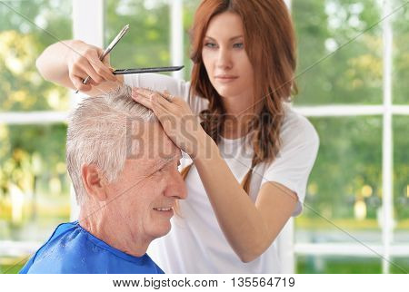 Man having a haircut  from female hairdresser at salon