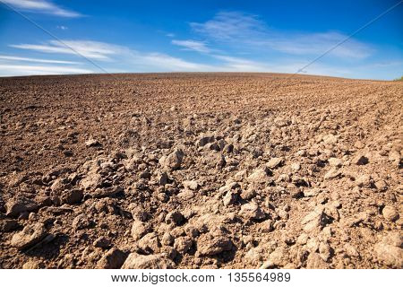 Agricultural background with plowed field and blue sky