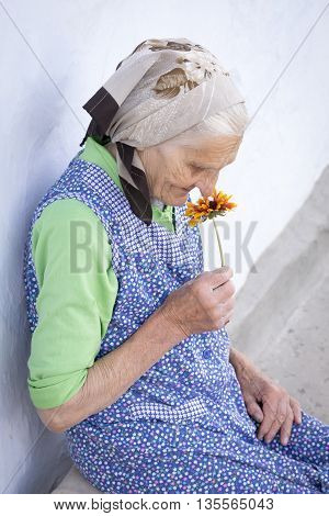 Senior woman sniffs a flower and thinking about his youth