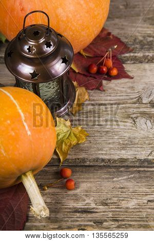 Pumpkinslantern and fall leaves on an old wooden table
