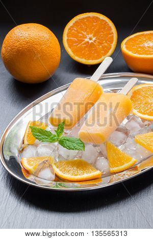Orange sorbet ice cream on silver plate with ice cubes orange pieces mint leaves near orange slices on a black background. Orange fruit sorbet ice cream popsicles. Vertical.