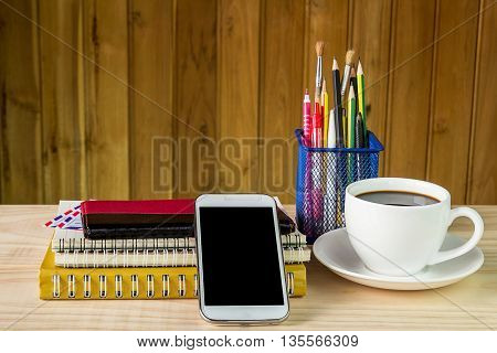 Smart phonecoffee cupand stack of book with calendar on wooden table background. Business concept