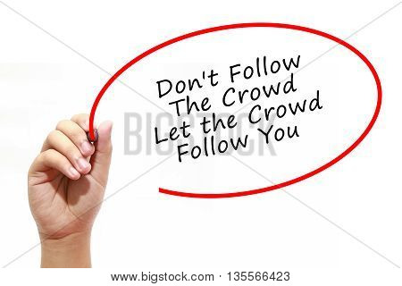 Man Hand writing Don't Follow The Crowd Let the Crowd Follow You with marker on transparent wipe board. Business internet technology concept.