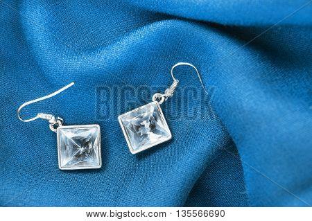 Topaz earrings on folded blue silk as a background