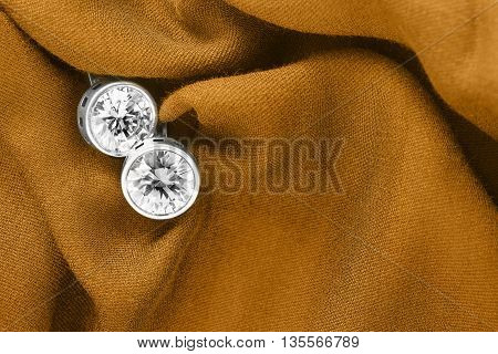 Diamond earrings on folded yellow silk as a background