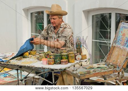 KYIV, UKRAINE - JUN 4, 2016: Artist in big hat working outdoor with paintings smeared in oil paint on June 4, 2016. Kiev is the 8th most populous city in Europe.