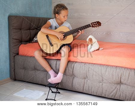 Little Girl Learning To Play A Musical Instrument