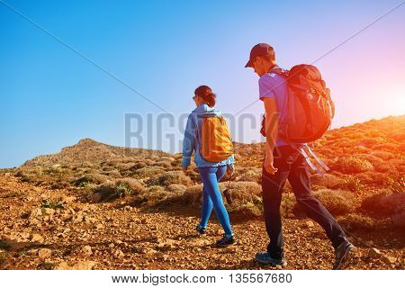 couple of travelers with backpacks walking on the trail against sea and blue sky at early morning. Balos beach on background, Crete, Greece
