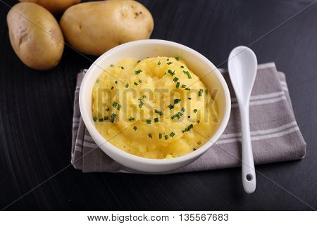 mashed potatoes in bowl on black background