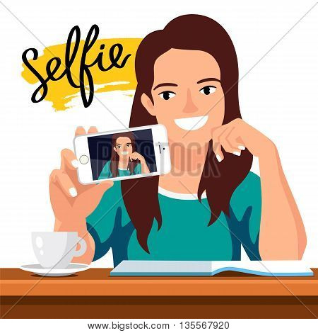 Young beautiful girl doing selfie on the phone at the table. Student in a cafe with a cup of coffee and a magazine. The trend calligraphy. The word
