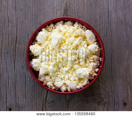 red plate with yellow fresh cheese on old wooden table grey cracked. top view close-up
