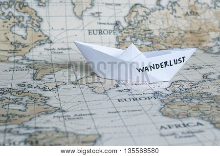 Wanderlust / Travel journey adventure concept with paper boat and world map background