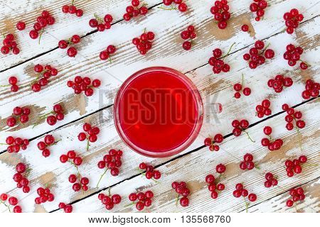 freshly squeezed red juice and bunches of red currants on a white wooden table with old paint. closeup flat lay