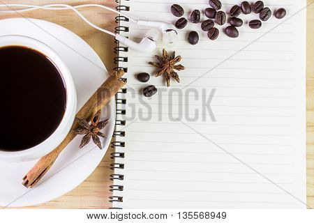 Coffee and open notebook with coffee beans on wooden table background. top view with copy space
