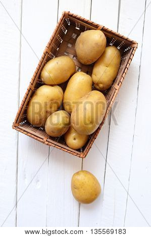 potato in basket on white wooden background