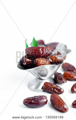 Dates in a bowl on a silver white background.