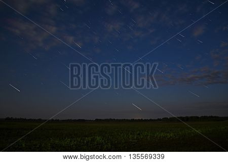 Scenic night landscape with clouds and stars in the form of tracks over the fields and forest taken with a long exposure