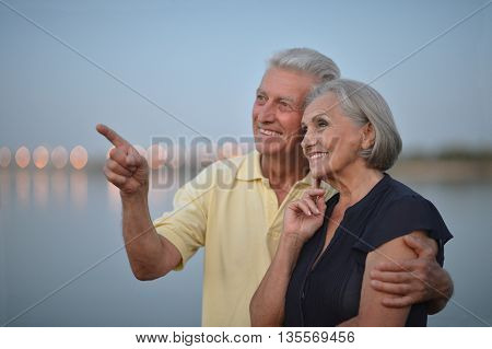 Happy senior couple  near river at summer, man pointing by his hand