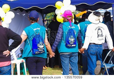 QUITO, ECUADOR - JULY 7, 2015: Tree persons praying and holding their hands in pope Francisco mass on Ecuador, volunteers helping.
